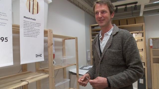 Ein Mann steht vor einem Ikea-Regal