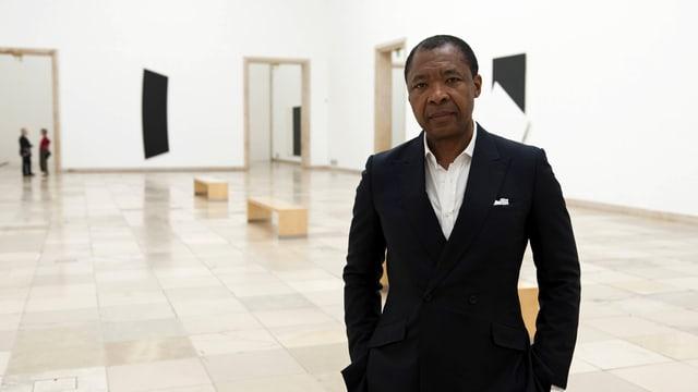 Okwui Enwezor in schwarzem Anzug und weissem Hemd in einer Ausstellung stehend.