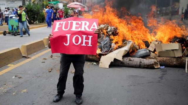 Demonstrant mit Transparent vor brennender Barrikade