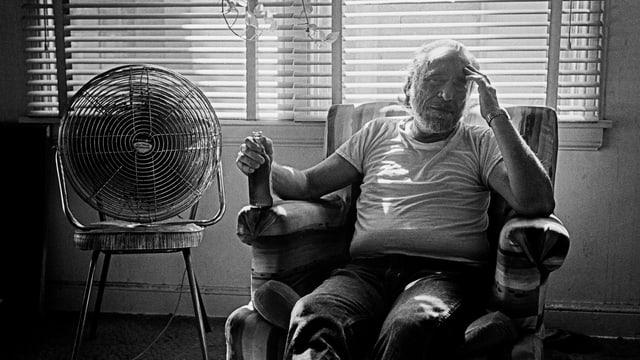 eine schwarz-weiss Aufnahme eines Mannes, der mit Bier im Schaukelstuhl sitzt