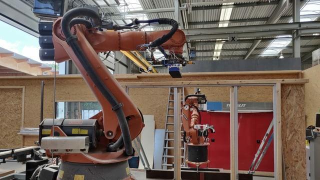 Zwei Roboterarme in einer Halle