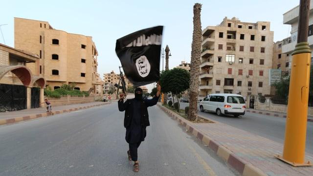 Ein IS-Mitglied läuft mit Gewehr und Flagge durch eine Strasse in Rakka.