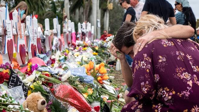 Eine Frau und ein junger Mann knien vor einem der 17 weissen Kreuze, die vor der Schule für die Opfer aufgestellt wurden.