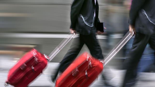 Zwei Geschäftsleute ziehen ihre Koffer durch den Flughafen