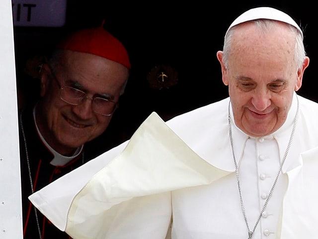Papst Franziskus steigt aus einem Flugzeug. Bertone steht hinter ihm.