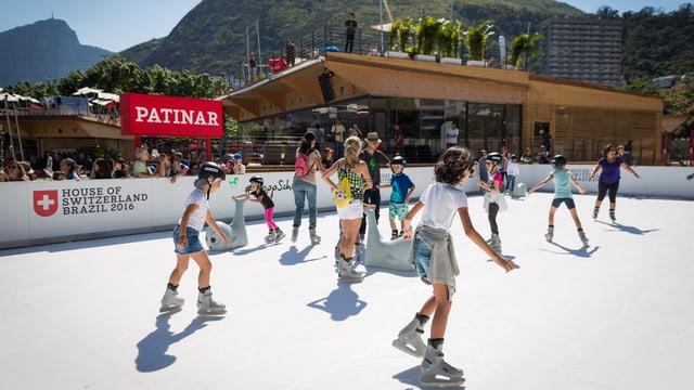 Visitaders sin la patinera sintetica en il «House of Switzerland».