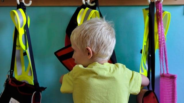 Ein Kindergärtner holt sich aus seiner Tasche ein Pausenbrot, daneben hängen die typischen Warndreiecke des TCS.