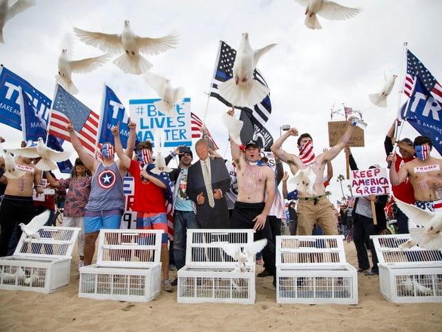 Trump-Befürworter lassen am Strand Tauben fliegen.