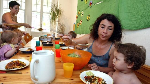 Zwei Betreuerinnen einer Kindertagesstätte mit Kindern beim Mittagessen.