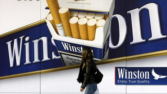 Zigarettenwerbung auf einem Plakat, davor läuft eine Passantin vorbei.
