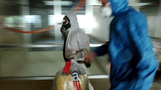 Zwei Männer in Schutzanzügen tragen Säcke mit Asbest verseuchtem Material weg