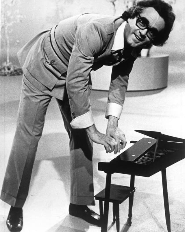 Michel Legrand spielt auf einem kleinen Klavier.