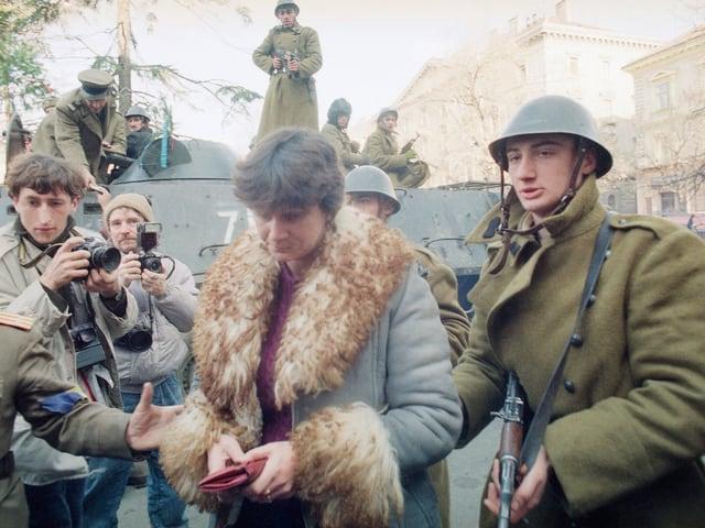 Frau, die von Soldaten abgeführt wird.