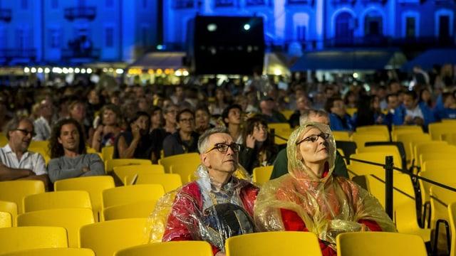 Zwie Personen in Regenmänteln auf einem Platz voller gelber Plastik-Stühle.