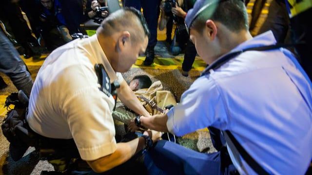 Polizisten legen einem Demonstranten Handschellen an