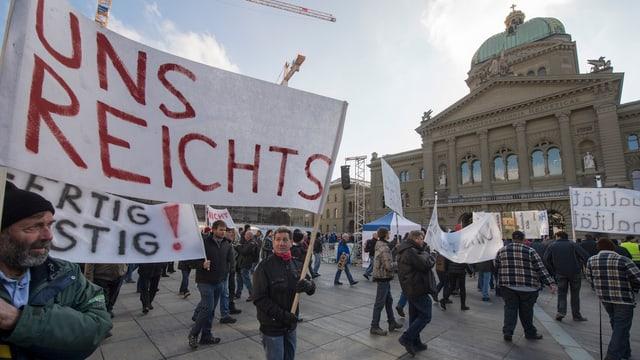 """Bauern demonstrieren auf dem Bundesplatz, auf einem Transparent steht """"Uns Reichts"""""""