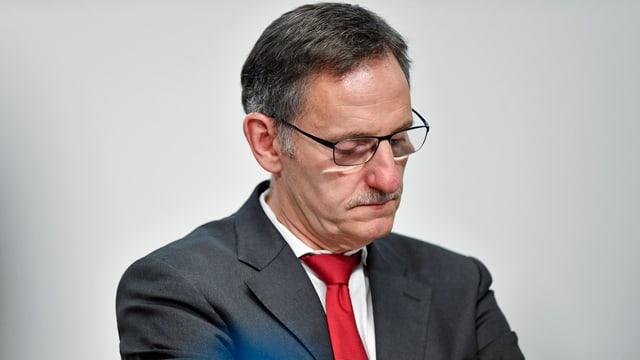 Ein Mann mit Brille blickt traurig nach unten.