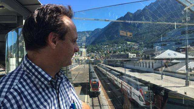 Il maletg mussa Stefan Engler che guarda sur ils binaris e la staziun da Cuira ora.