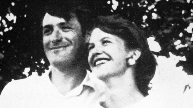 Hughes und Plath stehen lächelnd und Arm in Arm da.