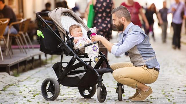 Ein Mann kniet auf der Strasse runter zu einem Kinderwagen und lächelt ein kleines Kind an.
