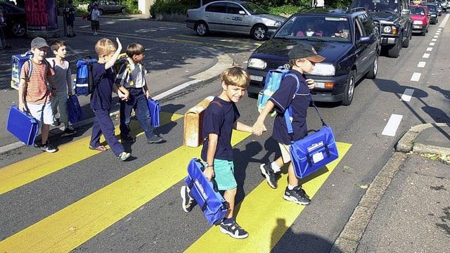 Schulkinder überqueren einen Zebrastreifen.