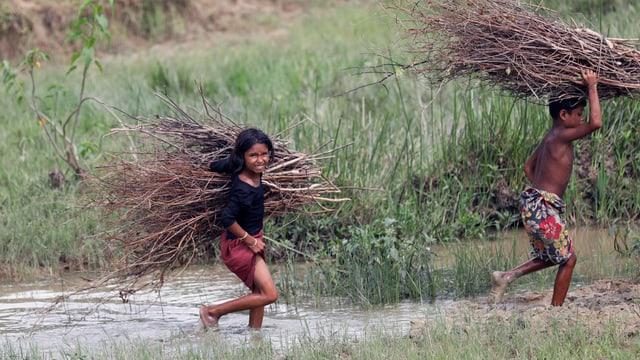 Mädchen und Junge der Rohingya-Minderheit sammeln Holz