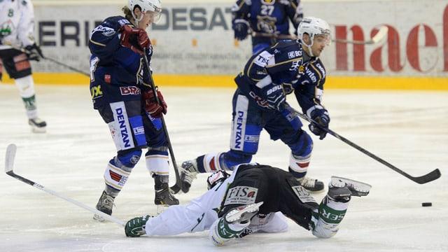 Ein Spieler des EHCO liegt auf dem Boden, um ihn herum mehrere Spieler von La-Chaux-de-Fonds. Aufgenommen im Spiel vom 23. Februar 2014.