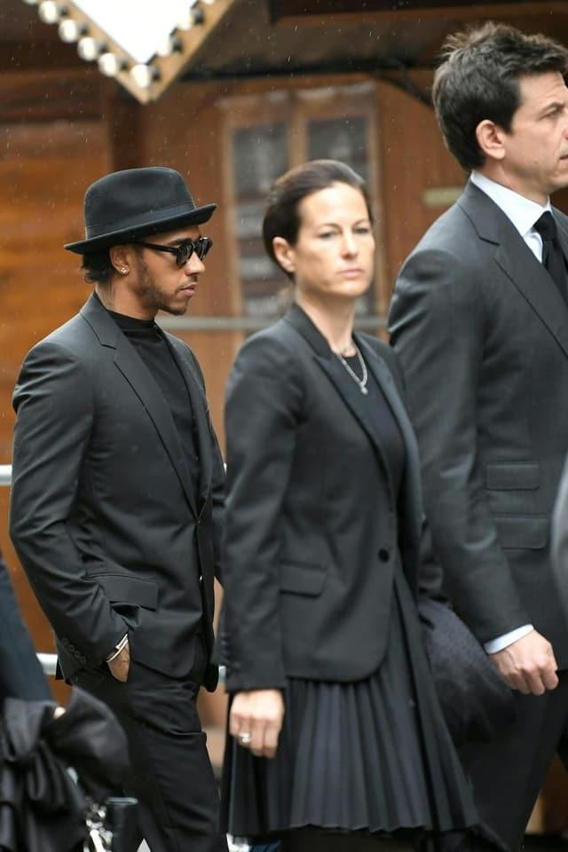 Formel-1-Weltmeister Lewis Hamilton in Schwarz gekleidet neben Laudas Ehefrau Birgit.