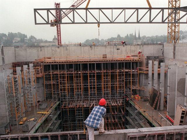 Die KKL-Baustelle mit viel rohem Beton, Kranen und einem Arbeiter.