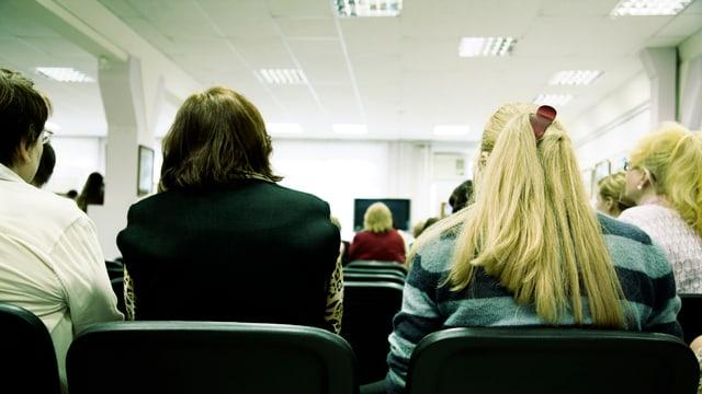 Interessierte Teilnehmer hören einem Dozenten zu.