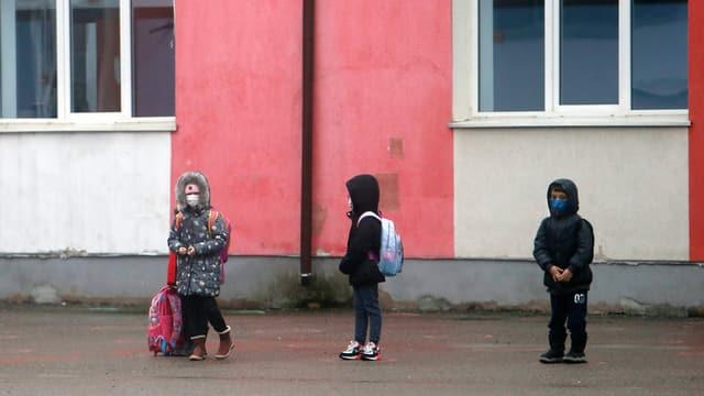 Kleine Kinder auf einem Pausenplatz mit Abstand in Bukarest, Rumänien