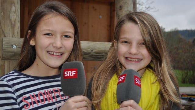 Annika und Sophie stehen im Freien und halten je ein Mikrofon in den Händen.