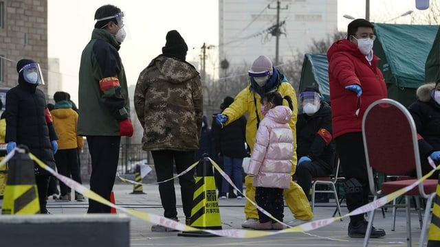 Zu sehen Leute, die in Peking für Coronatests anstehen.