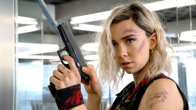 Vanessa Kirby mit einer Pistole in der Hand und Schürfungen im Gesicht.