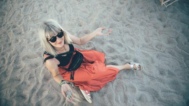 Tina Nägeli sitzt im Sand am Openair Frauenfeld.