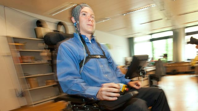 Forscher mit Steuerungskappe im Rollstuhl.