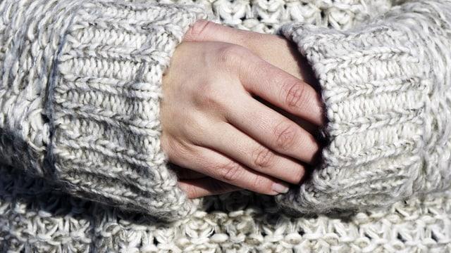 Frau verschränkt ihre Hände in die Ärmel ihres Wollepullis.