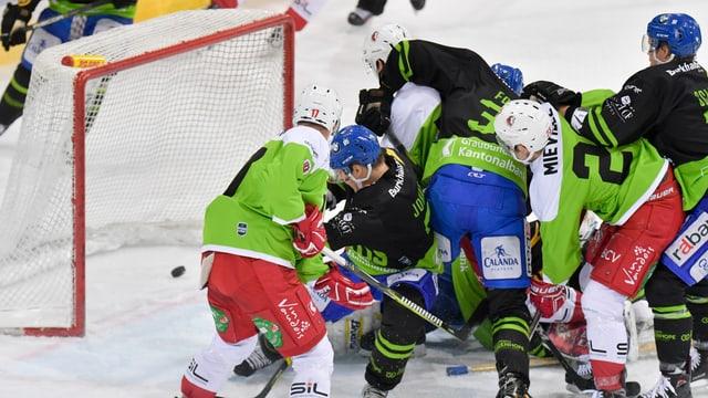Giugaders da hockey che cumbattan per il disc davant il gol.