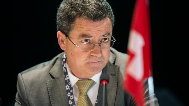 Rossier sitzt vor einem Mikrofon, unscharf im Bild auch eine kleine Schweizerfahne.