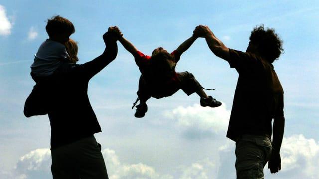 Ein Ehepaar mit zwei Kindern: Eines auf den Schultern eines Elternteils, eines springt an den Händen der Eltern in die Luft.