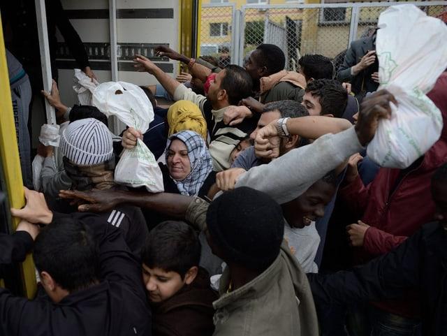Syrische Flüchtlinge stehen an um an Essen zu kommen.