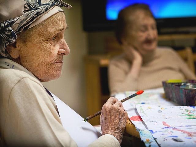 Eine alte Frau mit Kopftuch und Pinsel in der Hand.