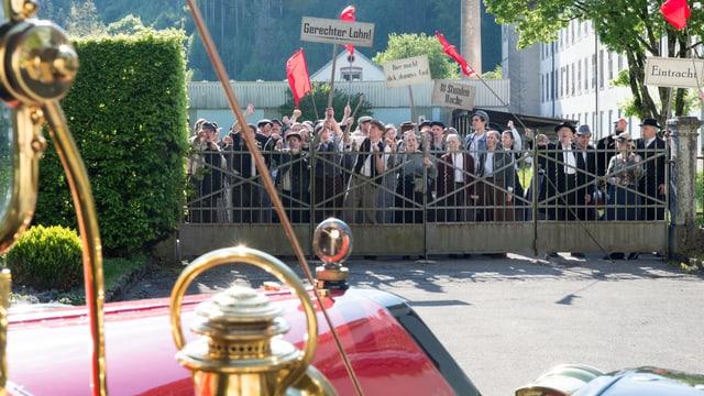 Arbeiterschaft demonstiert am Zaun der Villa, im Vordergrund das knallrote Auto