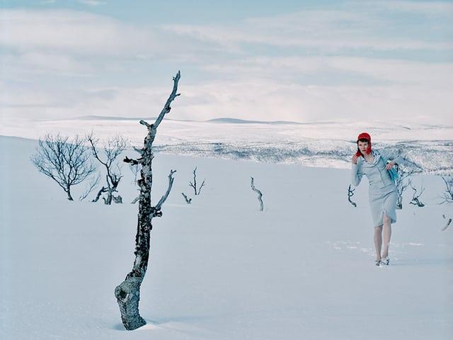 Ein Bild einer jungen Frau, die im Business-Outfit durch den Schnee läuft.