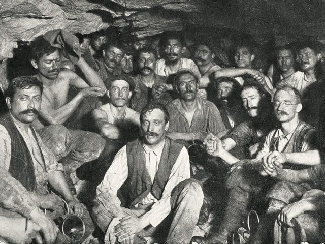 Nach dem Durchstich im Lötschbergtunnel: Viele Männer in dreckiger Arbeitskleidung schauen gebückt in die Kamera.