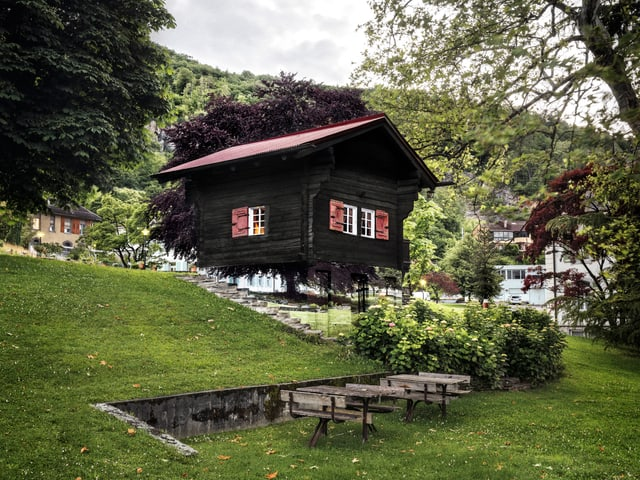 Ein kleines Haus, dessen Sockel die umliegende Landschaft zu spiegeln scheint.