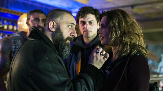 Ein Mann mit Bart und eine Frau stehen nahe voreinander und diskutieren. Im Hintergrund schauen zwei Männer zu, der eine hat ein verschlagenes Gesicht.