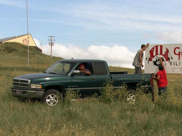 Filmstill: Ein Pickup-Truck und junge Männer, die ein Schild aufstellen.