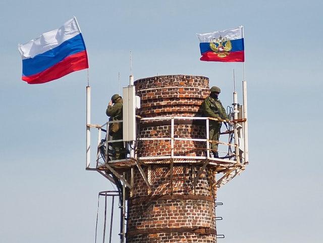 Wachturm mit zwei Soldaten und zwei russischen Flaggen drauf.