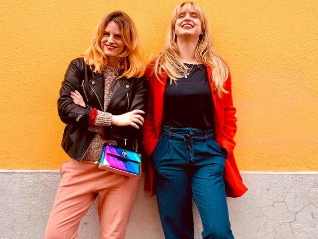 Zwei Frauen in bunter Kleidung vor gelber Wand